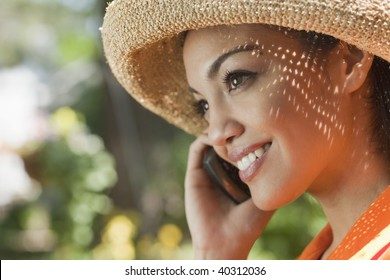 Close-up side view of a smiling young woman using a cell phone in an outdoor setting. Horizontal format.
