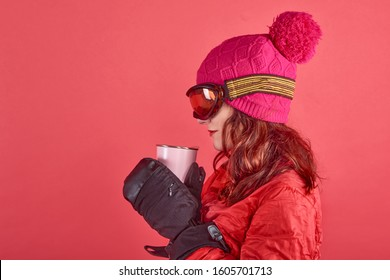 Closeup side view studio shot portrait woman wearing rad ski clothes and standing in red background with tinsel and ski mask
