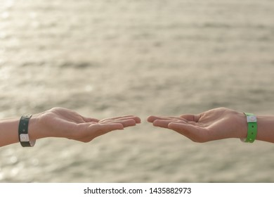 Closeup side view of two human hands wearing entrance wristbands isolated on blurry sea water background. Mother and son holding hands in gesture of demonstrating something virtual and invisible.