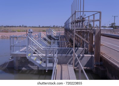 closeup side view of water control gates in a canal in the country on a bright sunny day
