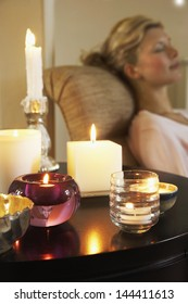 Closeup side view of a woman relaxing on sofa beside table with lit candles