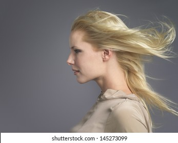 Closeup side view of a young woman with blond hair blowing in wind against gray background