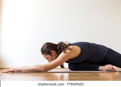 Close-up side view of a young woman working out at home, doing the Sleeping Swan yin yoga posture, medium length.