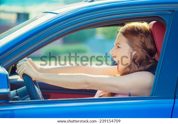 Closeup side window view displeased angry pissed off aggressive woman driving car shouting screaming at someone isolated traffic background. Emotional intelligence concept. Negative human emotion