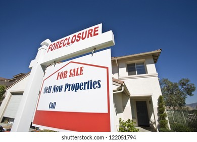 Closeup of sign board with house against blue sky