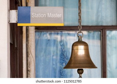 Closeup sign station master with a golden bell in train station. Traditional sound signaling on the platform at the railway station.