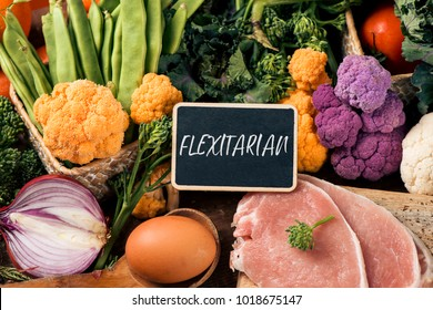 closeup of a signboard with the text flexitarian on a pile of some different raw vegetables, such as cauliflower of different colors, broccolini, or french beans, and some eggs and slices of meat