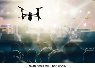 Closeup silhouette of Drone flying for taking video of Concert crowd and Music fanclub with show hand action which follow up the songer at the front of stage, musical and concert concept