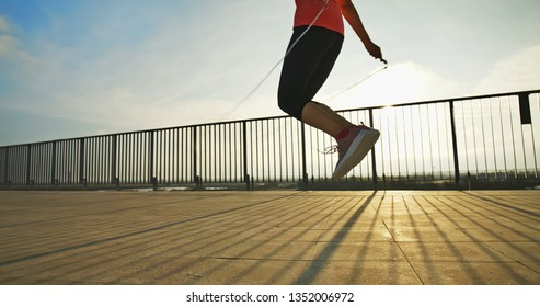 closeup silhouette of woman sport and rope skipping with sunset