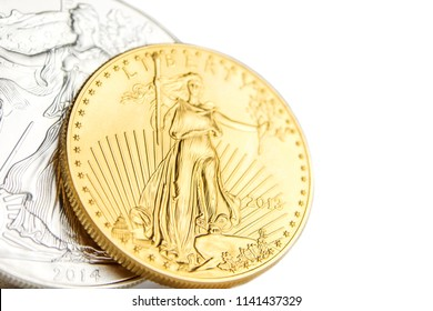 closeup of silver eagle and golden american eagle one ounce coins on white background placed on left side