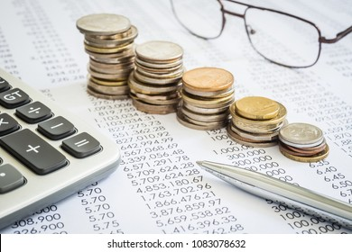 Closeup the silver modern pen on financial and  accounting reports with increase coin stacks, glasses and calculator in background. Concepts of tax planning and budget management.
