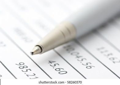 Close-up of silver pen on paper table numbers. Selective focus on top of pen.