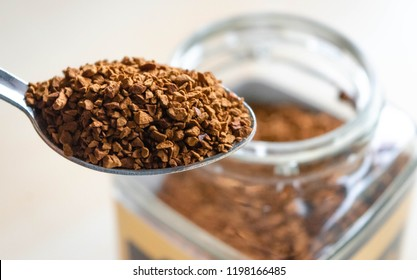 Closeup Silver spoon filled with soluble instant coffee granules powder on white background. A spoonful of instant coffee with open transparent glass jar in the background. with shallow depth of field