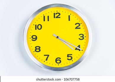 close-up of a silver and yellow wall clock.
