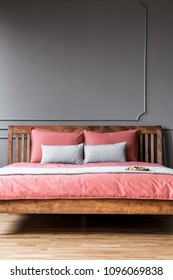 Close-up of a simple bed with wooden bedhead and pink sheets in dark, elegant bedroom interior with molding on dark walls. Real photo