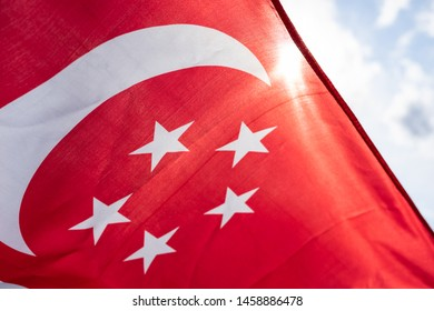 Close-up Singapura. Singapore flag waving on wind on cloudy sky background. Singapore Flag Day. Flag of Singapore fluttering in sunny rays high. Holiday,  National Day of Singapore Concept.