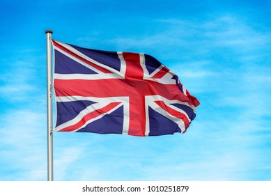 Closeup of single british union jack flag waving in the wind in front of blue sky