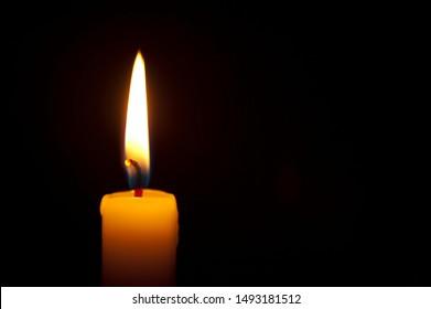 Close-up of single burning candle on black background. Copy space. Horizontal shot.
