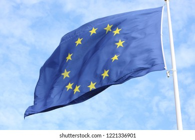 Closeup of single european flag with twelve yellow stars waving in the wind in front of blue sky