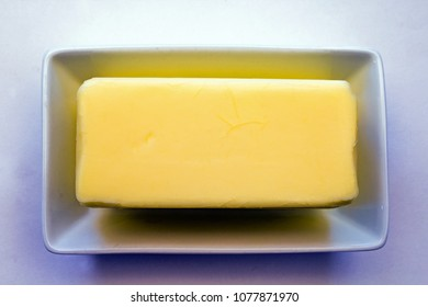 Closeup of a Single Stick of Butter on a White Ceramic Plate