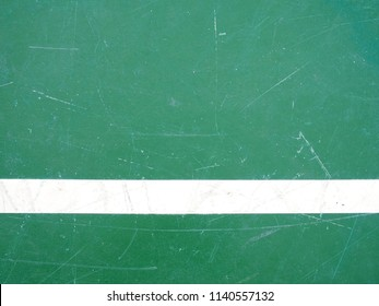 close-up single white line on green concrete floor with scratches texture, top view of old tennis hard court surface with copy space, abstract sport field background