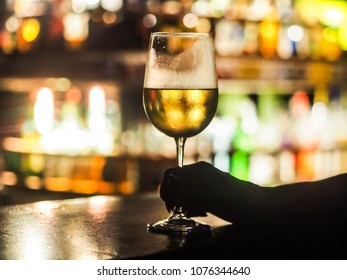 closeup of a single white wine glass standing alone on the bar counter with blury background