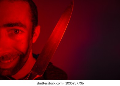 Closeup of sinister man holding a knife and looking at camera.