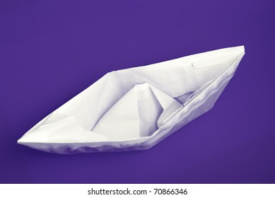 closeup of sinking folded paper ship in violet water with selective focus