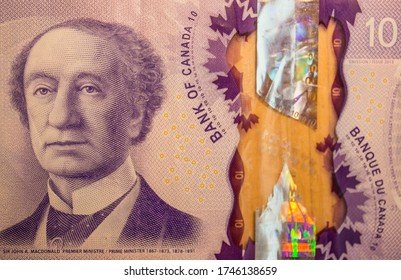 A closeup of Sir John A. Macdonald, Canada's first Prime Minister, on a ten dollar polymer bill which has a holographic stripe and is partly transparent.