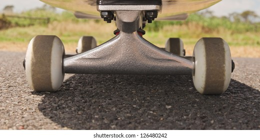 Closeup to skateboard trucks and wheels on rough asphalt road with blurred green trees and blue sky in background