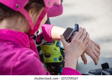 Close-up of skateboarder hands checking message on smartwatch.
