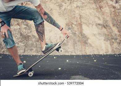 Closeup of skateboarder legs. Man riding skateboard outdoor.