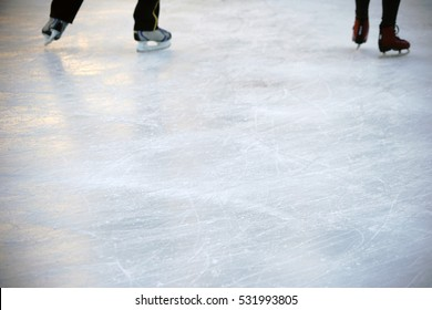 The close-up of the skates from ice skaters on an ice surface / Ice skating