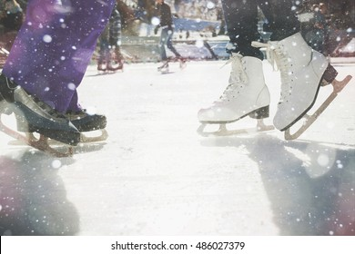 Closeup skating shoes ice skating outdoor at ice rink. Magical glitter of snowy snowflakes and bokeh. Healthy lifestyle and winter sport concept at sports stadium.