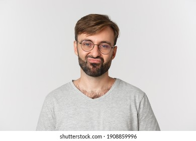 Close-up of skeptical bearded man in glasses and gray t-shirt, grimacing reluctant, standing over white background