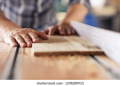 Closeup of a skilled carpenter sawing a piece of wood with a table saw while working alone in his woodworking studio