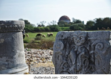 Close-up of a slab of carved stone with a column next to it. In the far distance, there are sheep.