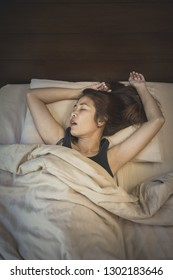 closeup sleeping woman on bed with arm raising and mouth opening
