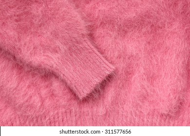 Close-up of sleeve of pink wool sweater.
