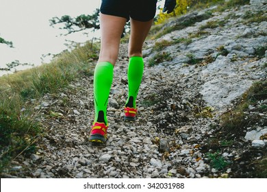 Closeup slender and beautiful legs of girl running uphill on track in compression socks. fitness and exercise in mountains