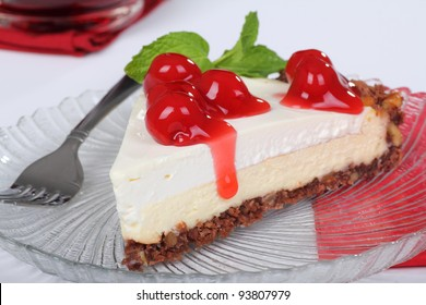Closeup of a slice of cheesecake with cherries and mint leaves on top on a glass plate