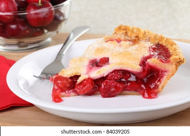 Closeup of a slice of cherry pie on a plate with a bowl of cherries in background