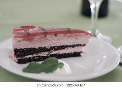 Closeup of a slice of dessert cake next to glass of champagne.