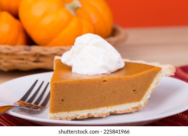 Closeup of a slice of pumpkin pie and whipped topping with pumpkins in background