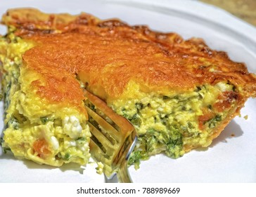Closeup of a slice of quiche with spinach and cheese sliced with a fork.