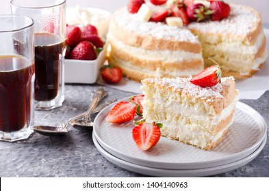 Closeup of a slice of sponge cake on the plate, glasses of coffee, bowl of strawberries, whole sponge cake on the background