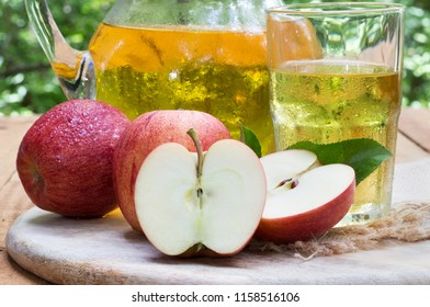 Closeup of a sliced apple with red apples and a glass and pitcher of juice in background