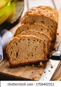 Closeup of sliced banana nut loaf cake on a wooden cutting board with bananas in background