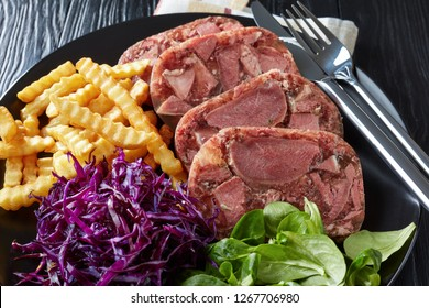 close-up of sliced beef tongue aspic served with french fries, green leaves and red cabbage salad on a black plate on a wooden table with mustard in a bowl, view from above