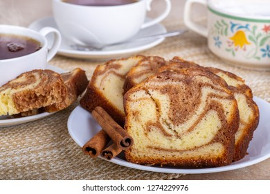 Closeup of sliced cinnamon swirl bread on a plate with two cups of coffee in background